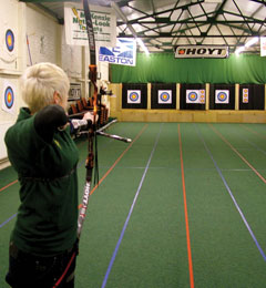 Lady taking aim at the indoor archery range
